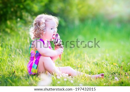 Funny happy toddler girl with curly hair wearing pink colorful summer dress sitting on a green lawn eating vanilla and chocolate ice cream cone in a sunny garden or park - stock photo