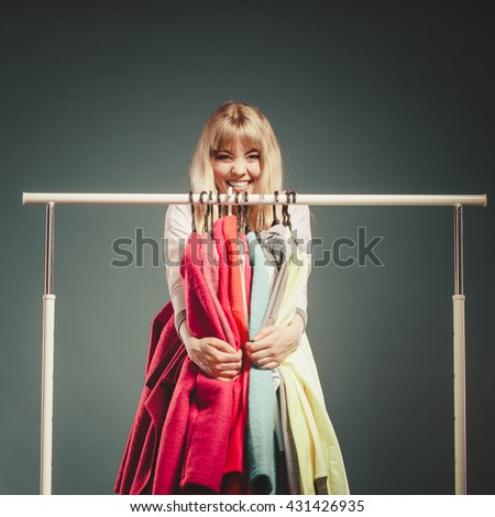 Funny happy woman girl taking grabbing all clothes coats and shirts in wardrobe. Young girl shopping in mall. Fashion clothing sale concept.