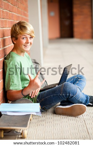 funny high school student giving funky hand sign - stock photo