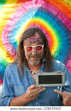 Funny hippie middle-aged man wearing blue denim shirt, headband, necklace and red sunglasses, while smiling and pointing towards a handheld blank small vintage blackboard - stock photo