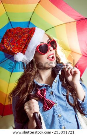 Funny hipster girl in heart shape sunglasses wearing xmas santa hat over rainbow umbrella background - stock photo