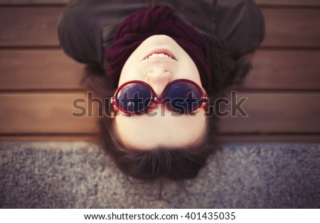 Funny hipster girl with pug nose in grey parka coat and sunglasses spending free time outdoors at spring day. Warm film color tones. - stock photo