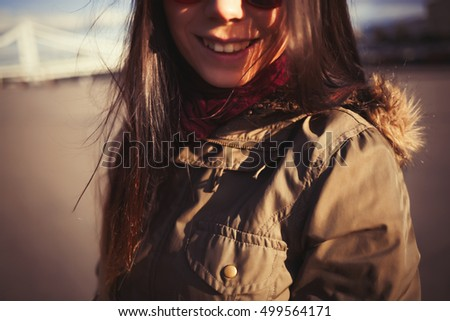 Funny hipster girl with pug nose in grey parka coat and sunglasses spending free time outdoors at spring day. Warm film color tones.