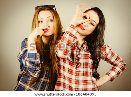 Funny hipster girls wearing plaid shirt making faces pretending to wear a mustache and glasses. Retro filter effect added. - stock photo