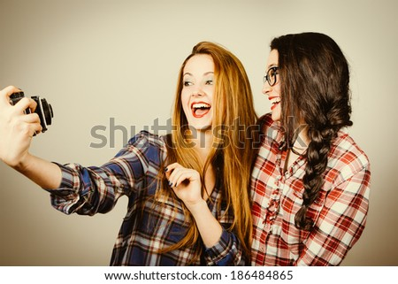 Funny hipster girls with plaid shirt and retro eye glasses making a selfie with an old film camera.Retro filter effect added. - stock photo