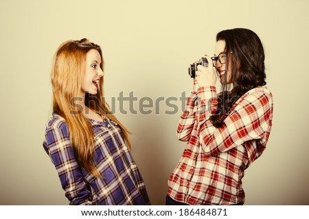 Funny hipster girls with plaid shirt and retro eye glasses portraying with an old film camera.Retro filter effect added. - stock photo