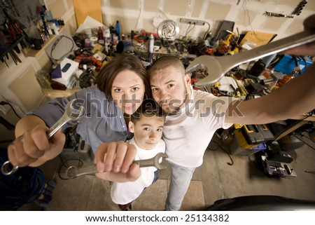Funny Hispanic family in garage with crescent wrenches - stock photo