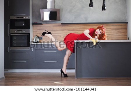 Funny housewife is cleaning the kitchen - stock photo