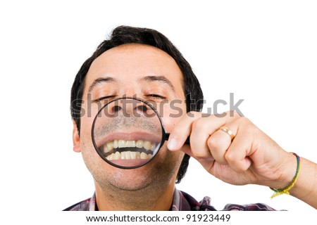 Funny image of a man with magnifying glass held up to face enlarging mouth and teeth.