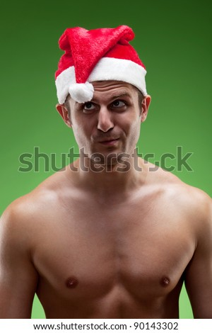 Funny image of a shirtless muscular man wearing Santa hat looking at his pompon, over green background - stock photo
