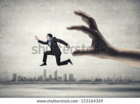 funny image of businessman trying to run away from hand - stock photo