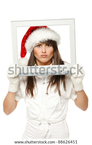 Funny image of discontent girl in Santa hat looking through the TV / computer screen frame, isolated on white background. - stock photo