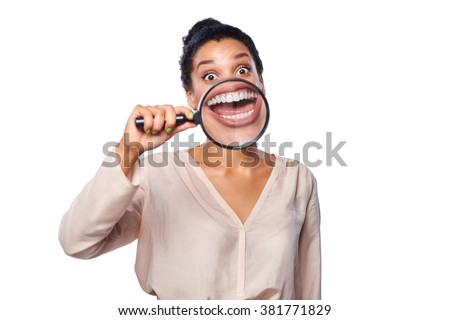 Funny image of happy excited female smiling and showing teeth through a magnifying glass, over white background - stock photo