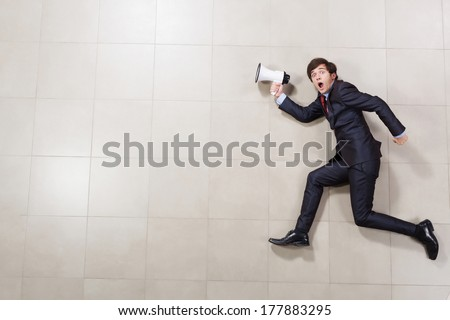 Funny image of running businessman holding megaphone - stock photo
