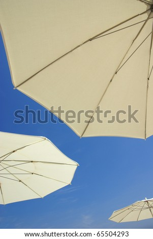 Funny image of three sunshades on the beach. - stock photo