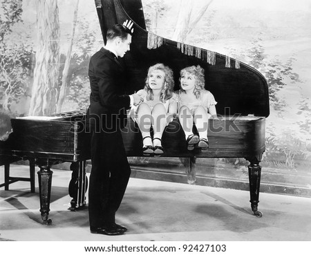 Funny image of twins sitting inside of a piano talking to a young man - stock photo