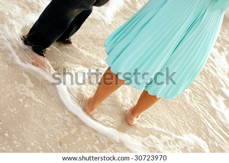 funny image of two well dress people standing in the ocean, showing from the waist down - stock photo