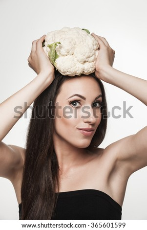 Funny image of woman showing cauliflower and smiling. Beautiful young brunette woman with slim body holding vegetables. Healthy eating and weight loss concept.  Studio white background. - stock photo