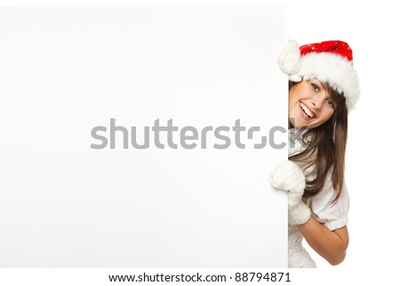 Funny image of young female wearing Santa hat pulling out a blank billboard with copy space applying effort, isolated on white background