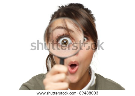Funny image of young surprised female looking at the camera through a magnifying glass, isolated on white background