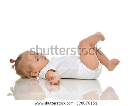 Funny Infant child baby girl in diaper lying on a back and looking on her legs isolated on a white background