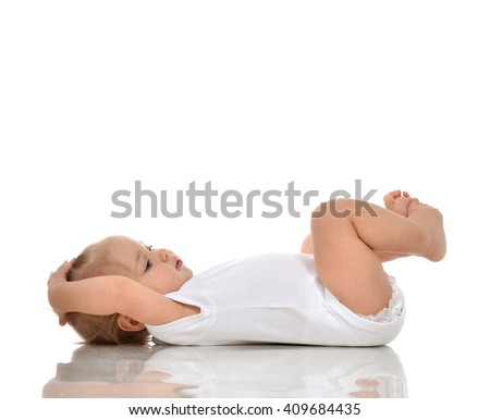 Funny Infant child baby girl in diaper lying on a back and looking up isolated on a white background - stock photo