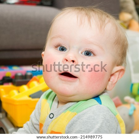 Funny infant in bright bode sitting on a floor with toys