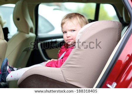 Funny kid, adorable toddler or baby girl sitting in the modern red car in a child seat locked with safety belt enjoying family vacation trip on summer weekend