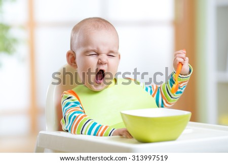 funny kid boy eating healthy food indoors - stock photo