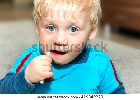 Funny kid brushing his teeth. Selective focus on face. - stock photo