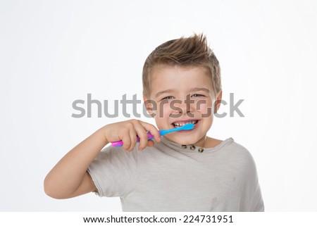 funny kid enjoys his toothbrush - stock photo