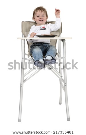 Funny kid in high chair eating seat ordering menu - stock photo