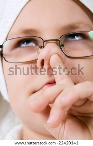 Funny kid picking in nose over white