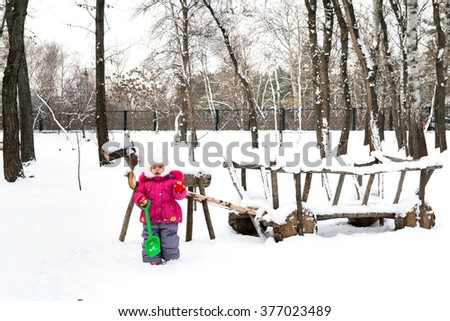 Funny kid playing with a shovel near a wooden cart with a horse on a winter day, games in the winter forest, wooden horse harnessed to a cart - stock photo