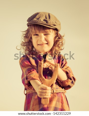 Funny kid shooting wooden slingshot. Retro toned image - stock photo