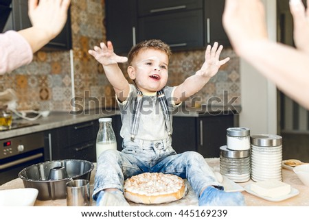 Funny kid sitting on the kitchen table in a rustic kitchen playing with flour and cake. He is covered in flour and looks funny. He is cute. He has arms raised in the air. - stock photo