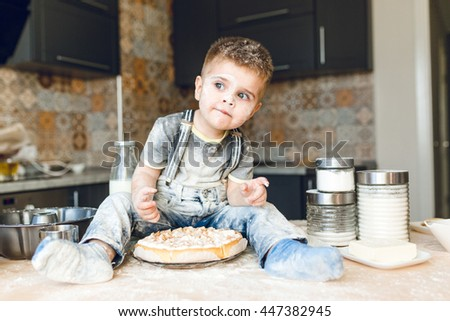 Funny kid sitting on the kitchen table in a rustic kitchen playing with flour and tasting a cake. He is covered in flour and looks funny. He looks curious. Milk and different jars stand on the table. - stock photo