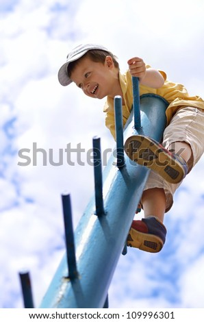 Funny kid sitting on the top of a high pole - stock photo