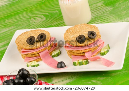Funny kid snack with crunchy crackers resembling faces - stock photo
