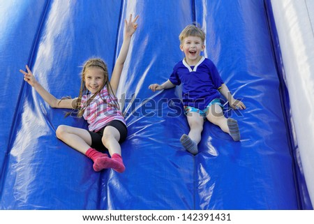 Funny kids and off the inflatable slides - stock photo