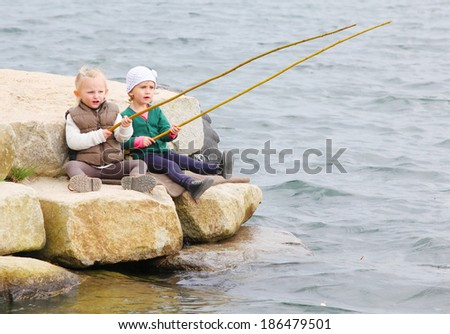 Funny kids catching fish. - stock photo