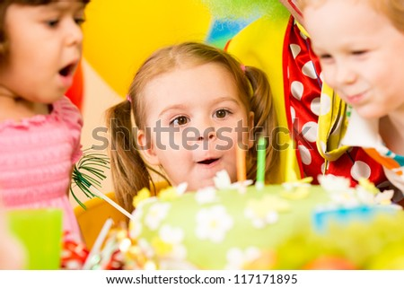 funny kids celebrating birthday party and blowing candles on cake - stock photo