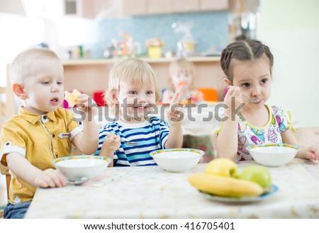 Funny kids eating in kindergarten - stock photo