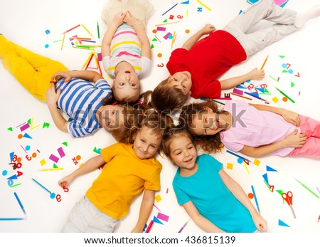 Funny kids laying among school office supplies