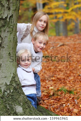 Funny kids playing peek a boo in autumn forest. - stock photo