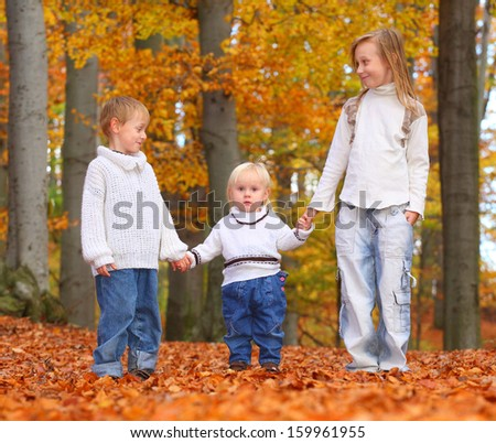 Funny kids walking in yellow foliage. Autumn in the city park.  - stock photo