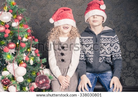 Funny kids with Santa hats at Christmas holiday near decorated christmas tree. New Year. Concept of family celebration - stock photo