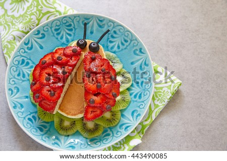 Funny ladybug pancakes with berries for kids breakfast - stock photo