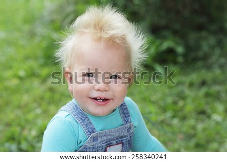 funny laughing baby in blue sitting outdoors - stock photo