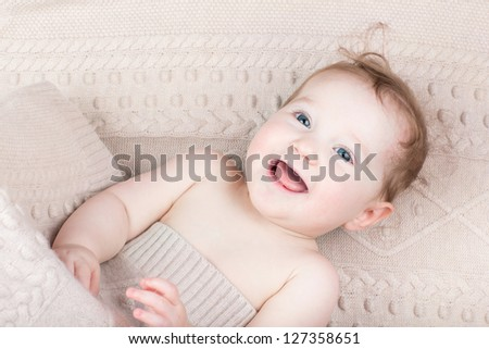 Funny laughing baby under a knitted blanket - stock photo